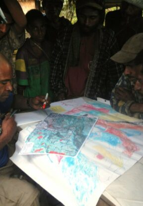 Mapping Officer transferring sketch maps onto a master copy in Papua New Guinea